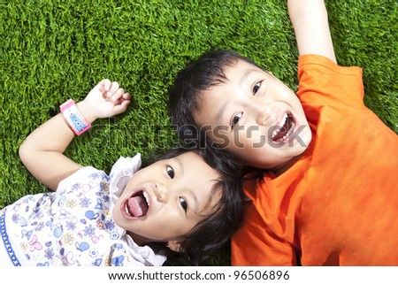 Closeup of happy young children lying on the green grass - stock photo