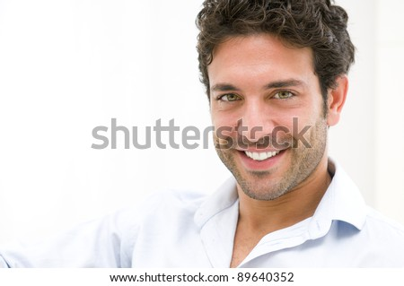 Closeup of happy young man looking at camera at home - stock photo