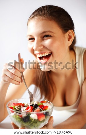 Closeup of happy young woman eating vegetable salad