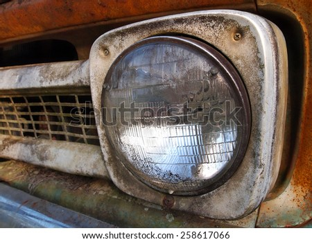 Closeup of headlight on the grill of a rusting vintage truck. - stock photo