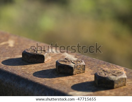 Closeup of heads of rusted bolts on bridge railing, with heavily blurred background giving look of watercolors. Deliberately shallow DOF with sharp focus on center bolt. - stock photo