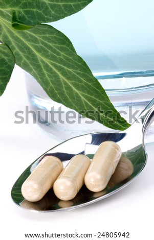 Closeup of herbal supplement pills inside spoon, fresh ivy leaves over glass of water best suited for alternative medicine ads. Shallow DOF. - stock photo