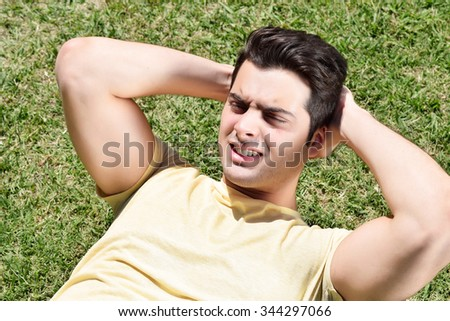 Closeup of hispanic young man exercising sit up in a park. Fit male athlete working out in summer. - stock photo