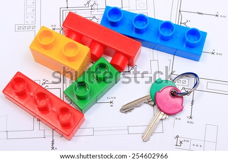 Closeup of home keys and heap of plastic colorful building blocks lying on construction drawing of house, concept of building house - stock photo