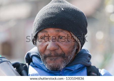 Closeup of homeless african american man. Outside during the daytime. - stock photo