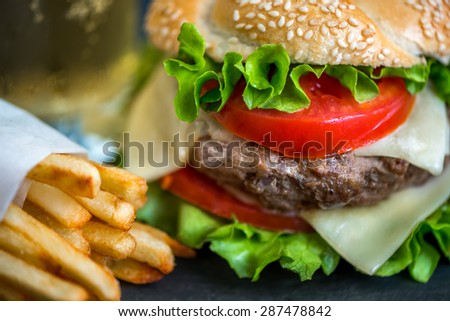 Closeup of Homemade Hamburger with Fresh Vegetables and French Fries - stock photo