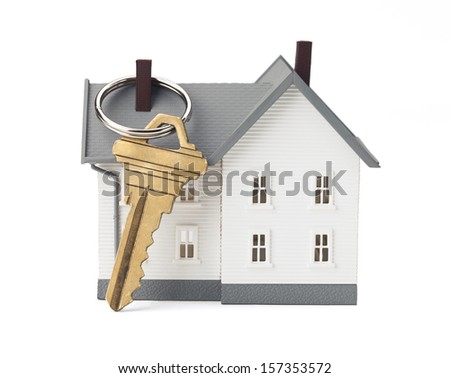 Closeup of house and key isolated on white background. Concept of real estate. Clipping path included. - stock photo