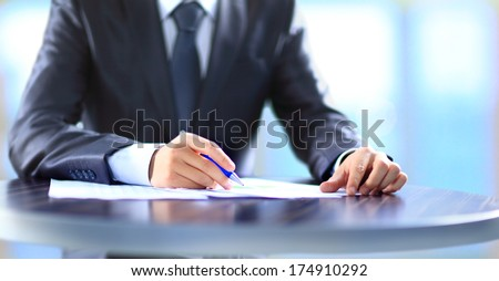 Closeup of human hand writing on a paper.