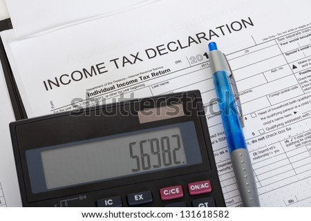 Closeup of income tax declaration, calculator and pen - stock photo