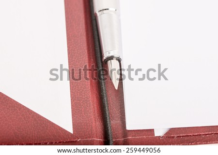 Closeup of ink pen on an open executive leather folder with blank white papers ready to take notes or start planning. - stock photo