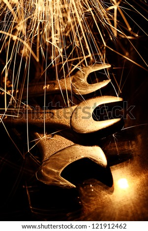 Closeup of iron spanners set and sparks light - stock photo