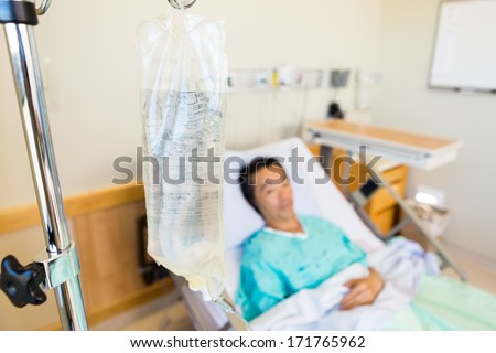 Closeup of IV bag with patient lying in background on hospital bed - stock photo