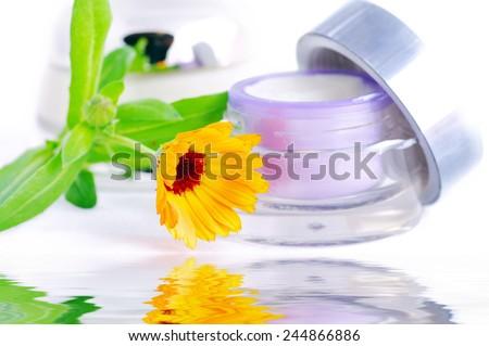 Closeup of jar of moisturizing face cream and fresh nasturtium flower  - stock photo