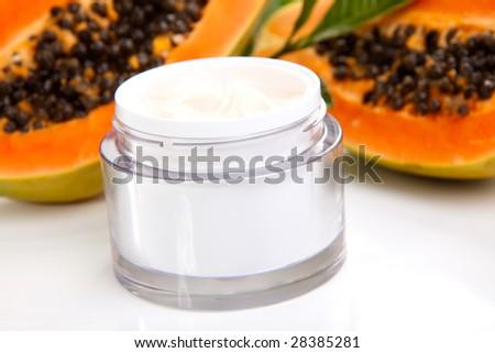 Closeup of jar of moisturizing face cream and fresh papaya - stock photo