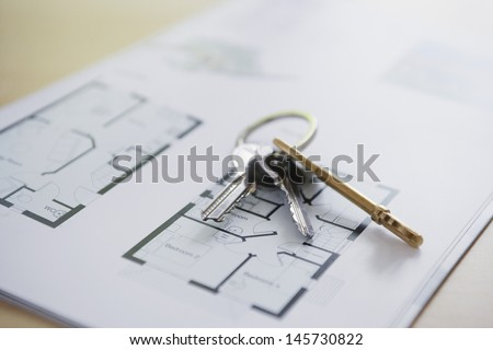 Closeup of keys on blueprint of new home - stock photo