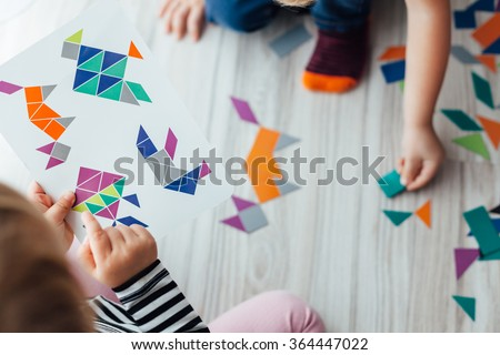 Closeup of Kids playing with geometric shapes, early learning - stock photo