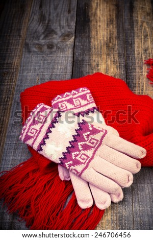 Closeup of knitted winter gloves and scarf on wooden board - stock photo