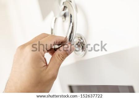Closeup of knocking on door with door knocker. - stock photo