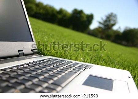 Closeup of laptop on a wide, green, grassy sports field