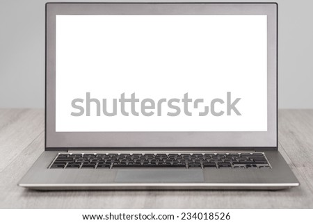 Closeup of laptop with blank white screen at wooden table - stock photo