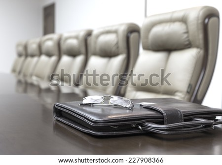 Closeup of leather briefcase on table in empty corporate conference room before business meeting in office