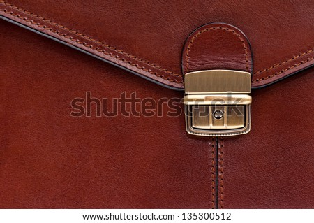 Closeup of leather briefcase with brass buckle - stock photo