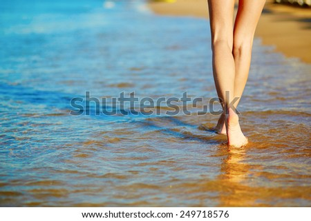 Closeup of legs of a woman walking on the beach