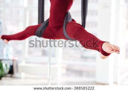 Closeup of legs of young woman doing twine on hammock in aerial yoga studio - stock photo