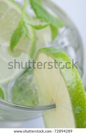 Closeup of lime in a glass of mojito with ice - stock photo