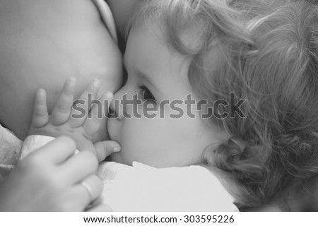 Closeup of little baby boy with curly hair in shirt sucking from female brest healthy maternity milk holding chest with hands sunny day outdoor black and white, horizontal picture