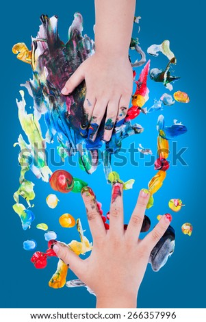 Closeup of little children hands doing finger painting with various colors on blue background, art education and creativity concept, top view - stock photo