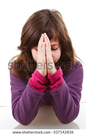 Closeup of little girl praying, looking down, hands in front - isolated on white - stock photo