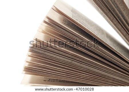 Closeup of lots of open pages of a book against white background with selective focus