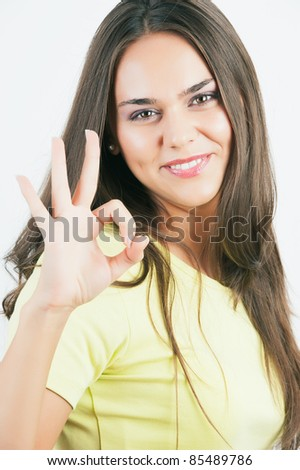 Closeup of lovely young woman gesturing ok hand sign over white background - stock photo
