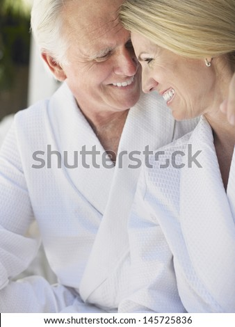 Closeup of loving middle aged couple in bathrobes - stock photo