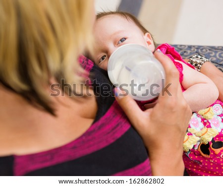Closeup of loving mother feeding milk to newborn baby girl while sitting on chair in hospital - stock photo