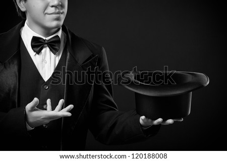 closeup of magician showing tricks with top hat isolated on dark background