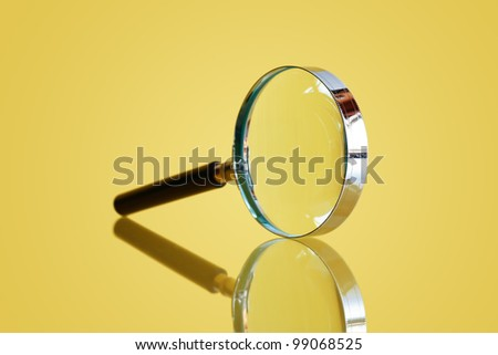 Closeup of magnifying glass on yellow background with reflection