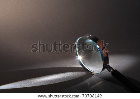 Closeup of magnifying glass standing on dark surface with beam of light - stock photo