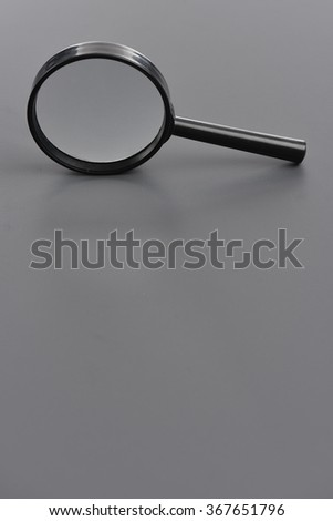 Closeup of magnifying glass standing on grey background - stock photo