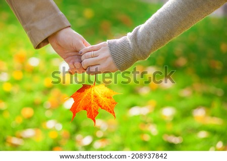 Closeup of male and female hands holding a red maple leaf - stock photo
