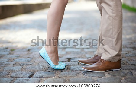 Closeup of male and female legs during a date - stock photo