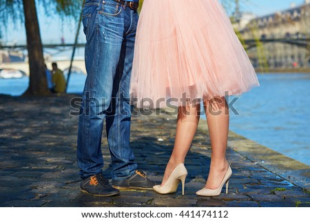 Closeup of male and female legs during a date. Romantic couple kissing on the Seine embankment in Paris - stock photo