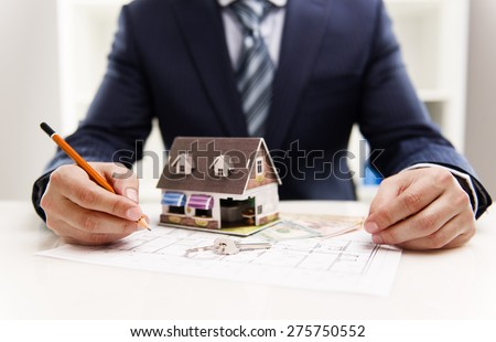 Closeup of male architect drawing heating system plan of customer house in the office. Real estate value and cost concept.  Shallow depth of field. - stock photo