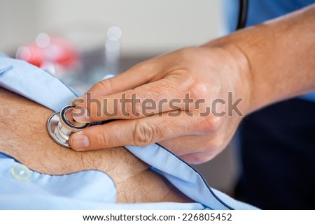Closeup of male caretaker examining senior man with stethoscope at nursing home - stock photo