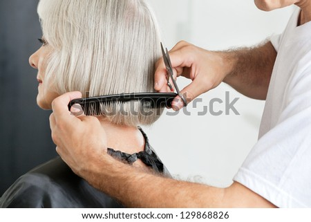 Closeup of male hairstylist measuring hair length before haircut in parlor - stock photo