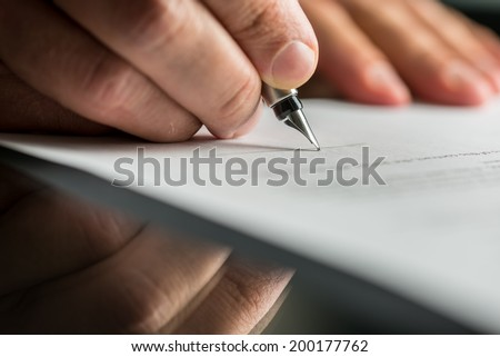 Closeup of male hand about to sign a business contract with a fountain pen.