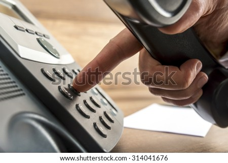 Closeup of male hand dialing a telephone number on black landline phone in a global communication concept. - stock photo