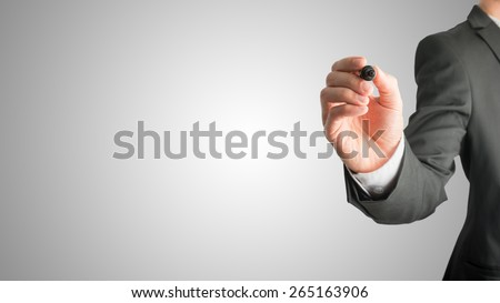 Closeup of male hand holding a black marker about to write something on a graduated grey background with central highlight and plenty of copyspace for your text.