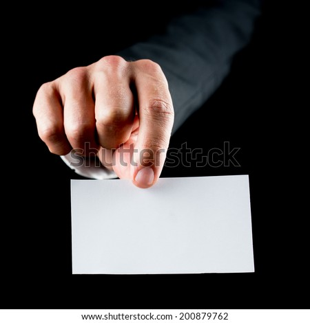 Closeup of male hand holding a blank white business card towards you. Over black background. - stock photo